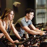 En kvinde og en mand træner på en motionscykel